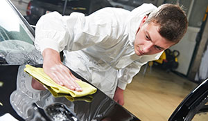 Technician providing car detailing services on vehicle hood